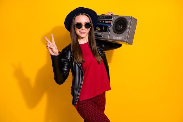Ritratto di ragazza allegra alla moda che porta boombox che mostra il segno della vittoria victory