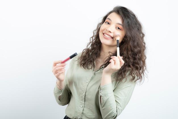 Ritratto di ragazza alla moda modello tenendo la spazzola con rossetto su un muro bianco.