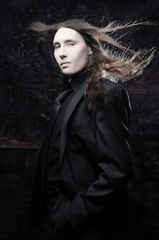 Ritratto di un modello maschile alla moda con i capelli lunghi su sfondo scuro. girato in studio