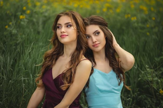 Ritratto di modelli di gemelli alla moda con trucco perfetto e acconciatura che si siede sull'erba verde