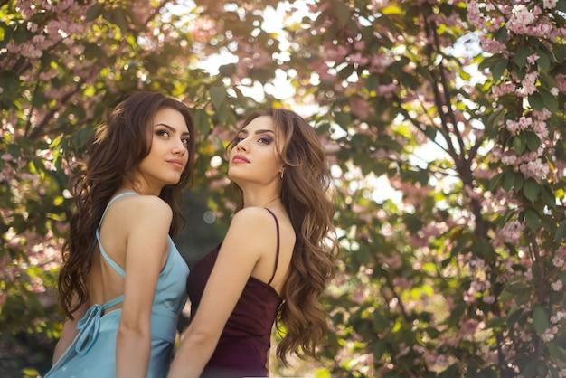 Ritratto di modelli di gemelli alla moda con trucco perfetto e acconciatura in piedi vicino a sakura