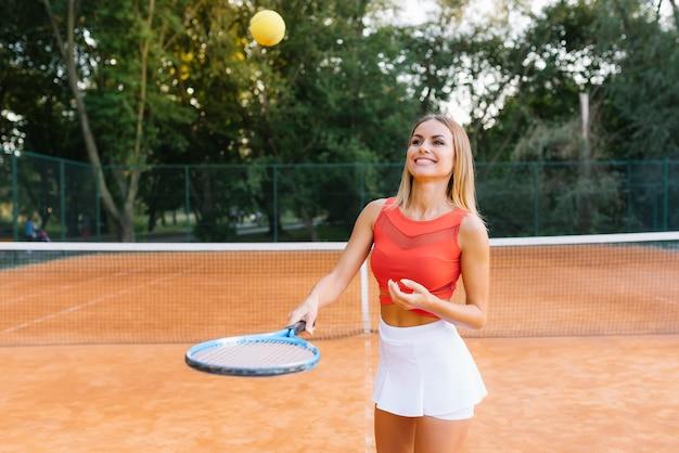 Ritratto di donna alla moda in abbigliamento rosso e bianco con racchetta da tennis in posa a rete da tennis sul campo