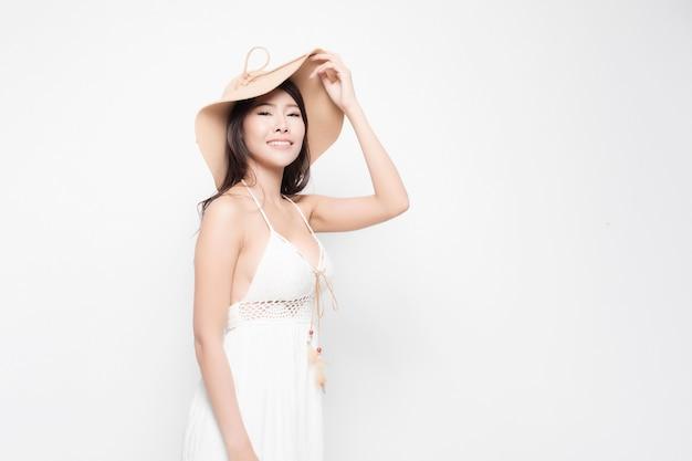 Ritratto di giovane donna alla moda sorride che indossa un abito estivo bianco e cappello da sole isolato su sfondo bianco.