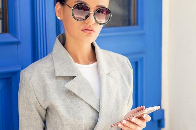Ritratto di giovane donna alla moda che indossa occhiali da sole utilizza lo smartphone vicino alla porta all'aperto.