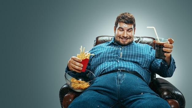 Ritratto di uomo caucasico grasso che indossa jeans e whirt seduto in una poltrona marrone su sfondo grigio sfumato. guardare la tv beve cola, mangia patatine, patate fritte, ride. sovrappeso, spensierato.
