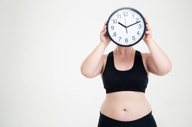 Ritratto di una donna grassa che si copre il viso con un orologio da parete isolato su un muro bianco