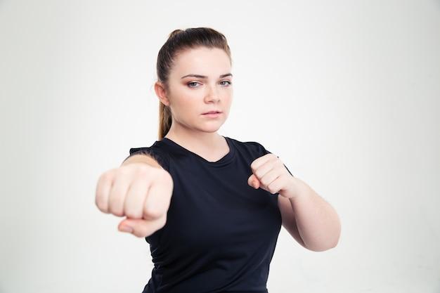 Ritratto di una donna grassa in abbigliamento sportivo che colpisce isolato su un muro bianco