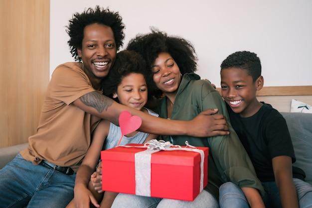 Il ritratto di padre e figli si congratula con la madre per la festa della mamma e le fa i regali a casa