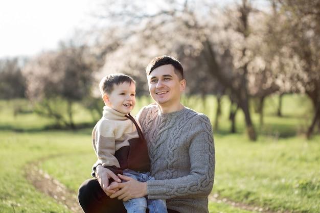 Ritratto di un padre e di un figlio in maglioni lavorati a maglia sullo sfondo di un albero in fiore in primavera.