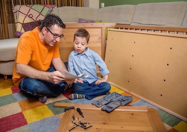 Ritratto di padre e figlio con strumenti che leggono le istruzioni per assemblare un nuovo mobile per la casa. concetto di svago per famiglie