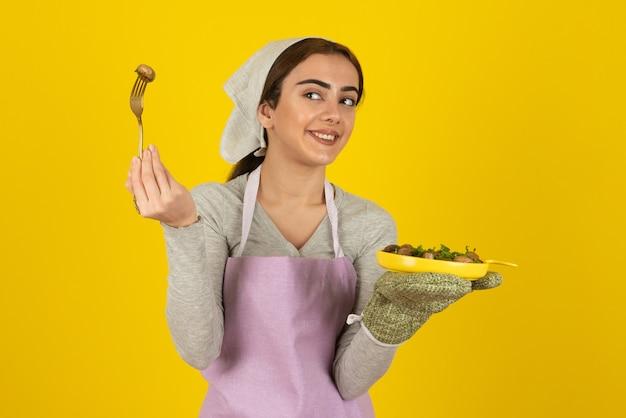 Ritratto di cuoca in grembiule viola in piedi con piatto di funghi fritti.
