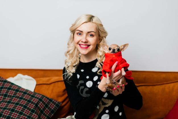 Ritratto di una donna in abiti scuri con un cagnolino insieme su sfondo chiaro di natale