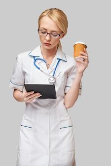 Ritratto di un medico femminile che tiene la tazza di caffè di carta e che tiene il rilievo del pc della compressa
