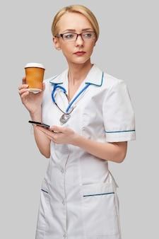 Ritratto di una dottoressa che tiene tazza di caffè di carta e parla al telefono