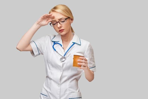 Ritratto di un medico femminile che tiene tazza di caffè di carta