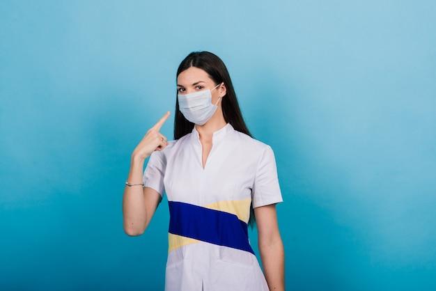 Ritratto del medico femminile in una mascherina medica che osserva via isolato sull'azzurro