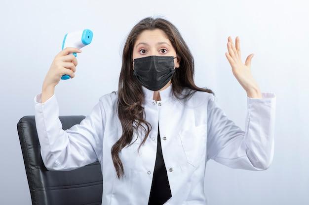 Ritratto di dottoressa in mascherina medica e camice bianco che tiene termometro.