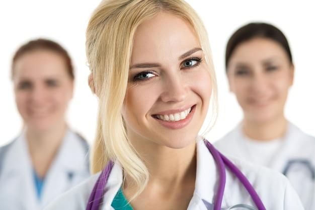 Ritratto di donna medico circondato da equipe medica, guardando e sorridente. concetto di sanità e medicina.