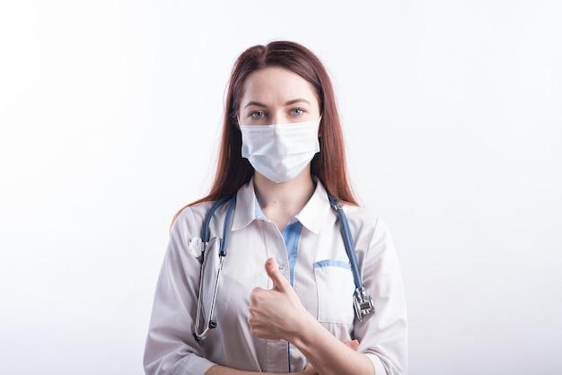 Ritratto di una dottoressa in uniforme bianca che mostra un pollice gesto di approvazione in studio su uno sfondo bianco