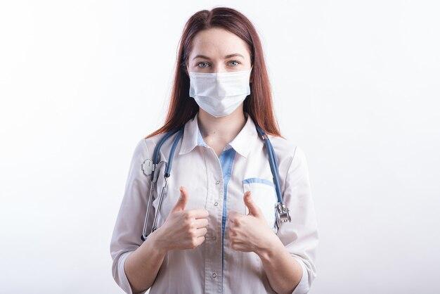 Ritratto di una dottoressa in uniforme bianca che mostra un pollice di gesto di approvazione