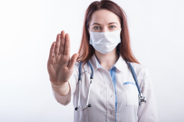 Ritratto di una dottoressa in uniforme bianca che mostra un gesto di stop