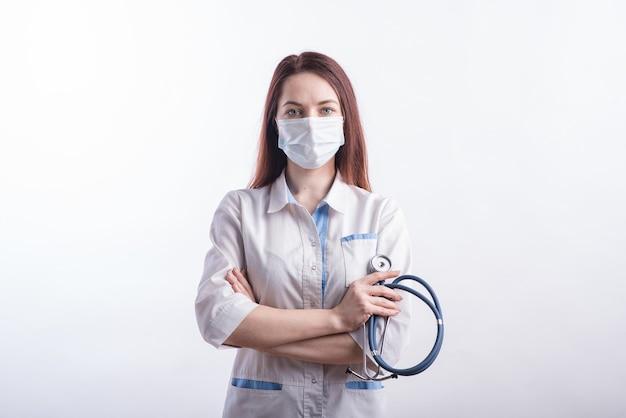 Ritratto di una dottoressa in uniforme bianca con una mascherina medica sul viso