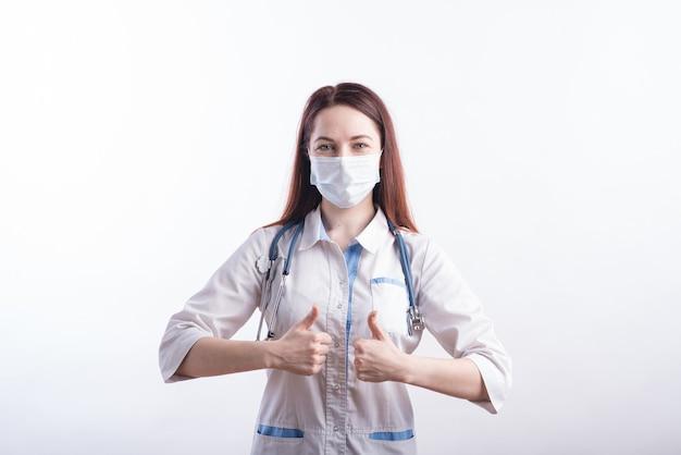 Ritratto di una dottoressa in uniforme bianca con una mascherina medica