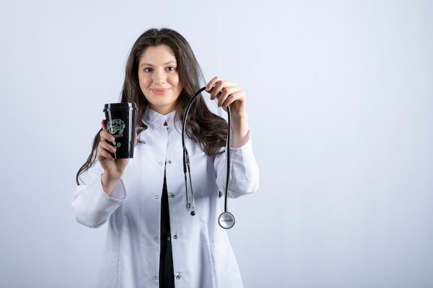 Ritratto di donna medico con lo stetoscopio e la tazza di caffè in piedi sul muro bianco.