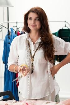 Ritratto di donna sartoria in piedi al suo atelier e tenendo un paio di forbici su misura