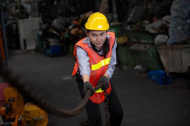 Ritratto di ingegnere femminile in piedi contro l'ambiente della macchina in fabbrica