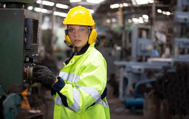 Ritratto di donna ingegnere che lavora sulla macchina cnc in piedi contro l'ambiente di fabbrica.