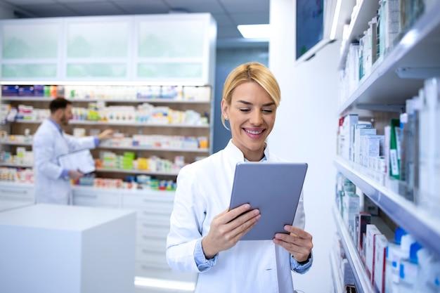 Ritratto di donna farmacista esperto che lavora su tablet in farmacia negozio dallo scaffale con farmaci.
