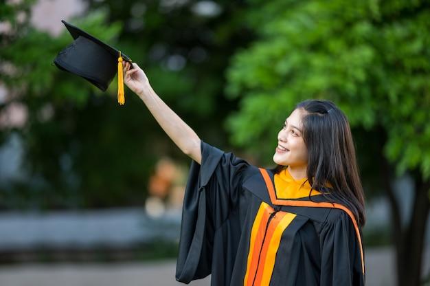 Ritratto laureato universitario femminile laureato che tiene un cappello nero