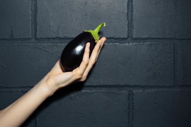 Ritratto di mano femminile che tiene una melanzana, sullo sfondo scuro.