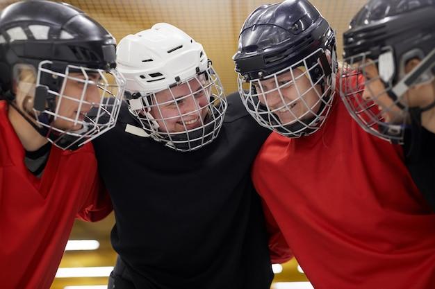 Ritratto della squadra femminile di hockey che si stringe felicemente prima della partita di sport