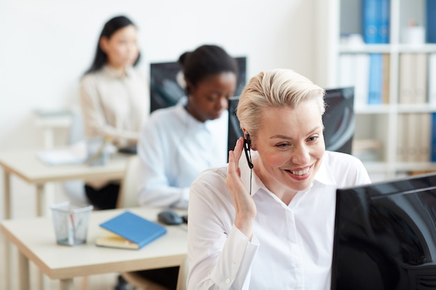 Ritratto di operatori di hotline femminili seduti alle scrivanie in fila, concentrarsi sulla donna sorridente che parla al cliente tramite auricolare