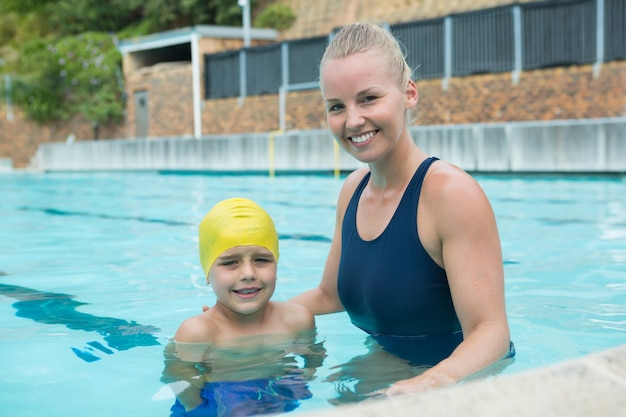 Ritratto di donna istruttore e giovane ragazzo in piedi in piscina