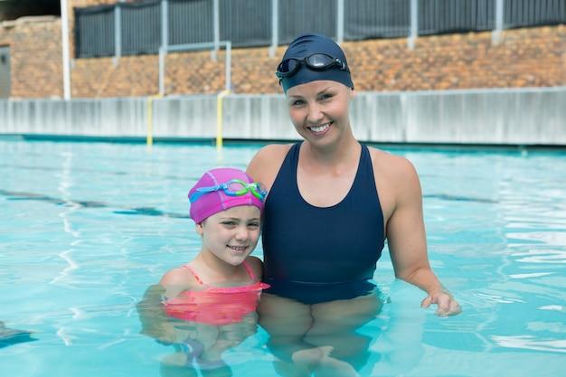 Ritratto di donna istruttore e giovane ragazza in piedi in piscina
