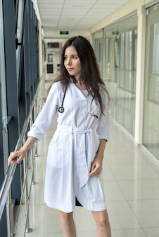 Ritratto di donna stagista operatore sanitario in piedi nel moderno corridoio dell'ospedale. concetto medico