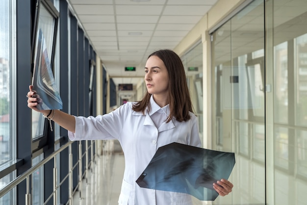 Ritratto di infermiera femminile stagista esaminando un paziente a raggi x in ospedale moderno. salutare