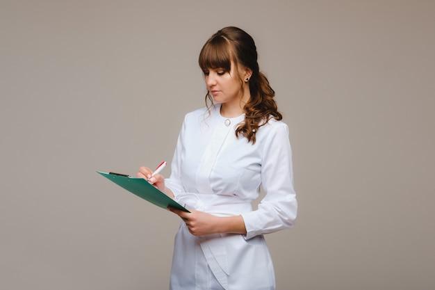 Ritratto di un operaio medico di sesso femminile in uno sfondo grigio con un referto medico. ragazza medico con un blocco note.