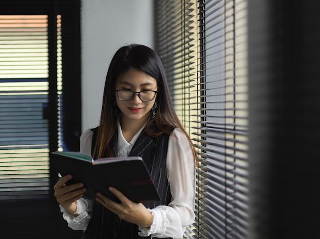 Ritratto di lavoratore di ufficio femminile lettura libro di pianificazione in piedi accanto alla finestra nella stanza dell'ufficio