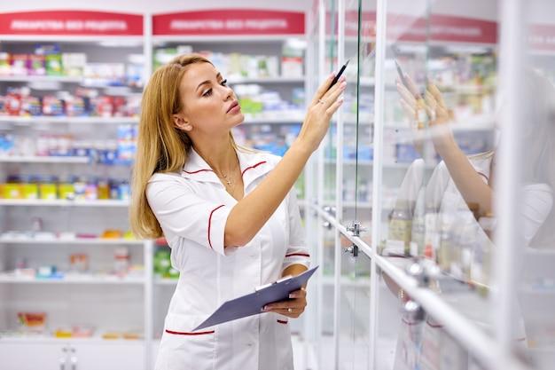 Farmacista femminile ritratto iscritto negli appunti in farmacia