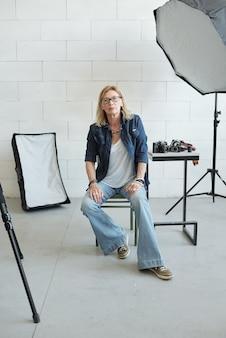 Ritratto di fotografo femminile in abito denim seduto su uno sgabello in studio fotografico pieno di luce