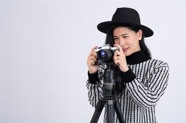 Ritratto di fotografo femminile in possesso di una fotocamera professionale su treppiede e scattare immagini su grigio