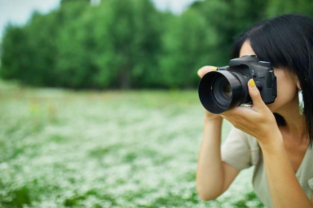 Il ritratto del fotografo femminile prende la foto all'aperto sul paesaggio del giacimento di fiore che tiene una macchina fotografica, macchina fotografica digitale della tenuta della donna nelle sue mani. fotografia naturalistica di viaggio, spazio per il testo, vista dall'alto.