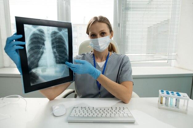 Ritratto di donna radiologa in maschera e guanti seduto alla scrivania con tastiera del computer e rack per provette e che ti spiega l'immagine a raggi x