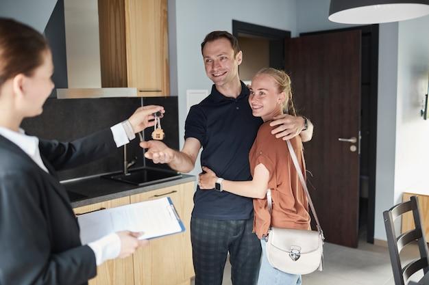 Ritratto di agente immobiliare femminile che dà le chiavi a una giovane coppia felice che acquista una nuova casa, copia spazio