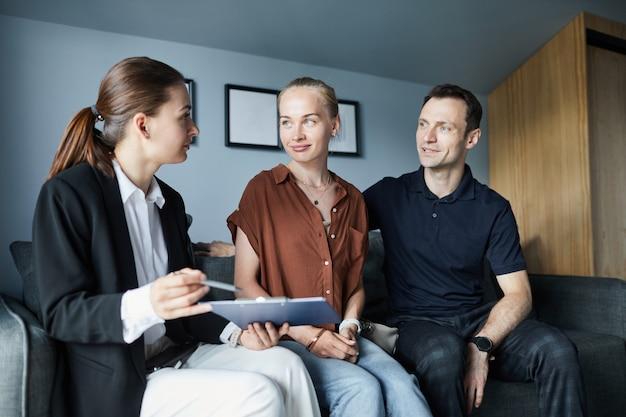 Ritratto di un agente immobiliare femminile che firma un contratto con una giovane coppia che acquista una nuova casa, copia spazio