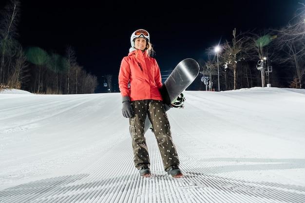 Ritratto di snowboarder femminile che indossa il casco bianco e giacca rossa in piedi con lo snowboard al pendio serale. concetto di sport invernali